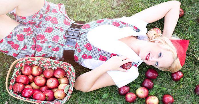 liegende Frau mit Korb voller Äpfel neben sich