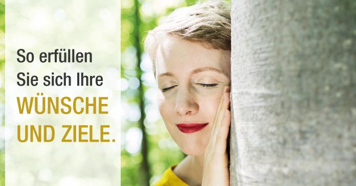 Frau leht mit geschlossenen Augen am Baumstamm